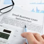Hand With Pen And Calculator On Business Loan Application Form